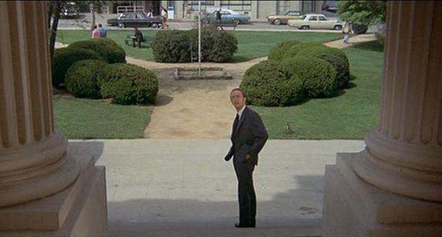 """Widok w kierunku placu przed budynkiem, zza kolumn - kadr z komedii """"How to Frame a Figg"""" (1971)"""