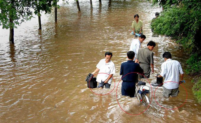 Północnokoreańscy oficjele ponoć udali się na zalane powodzią tereny, czego dowodem miała być m.in. ta fotografia. Szkoda, że ich nogi urywają się nad wodą, a sami nie rzucają cieni
